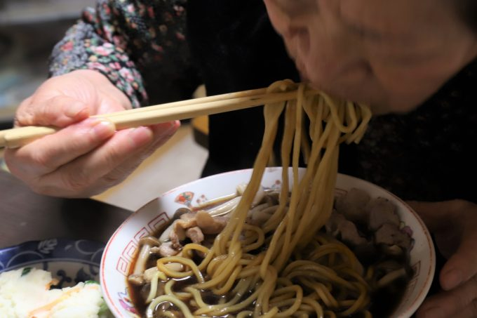 インスタントの富山ブラックラーメン(麺屋いろは)を食べている祖母(おばあ)