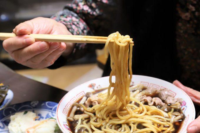 インスタントの富山ブラックラーメンの麺を箸で摘まんで持ち上げているところ