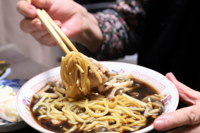 インスタントの富山ブラックラーメン(麺屋いろは)の麺を祖母(おばあ)が箸で摘まんでいるところ