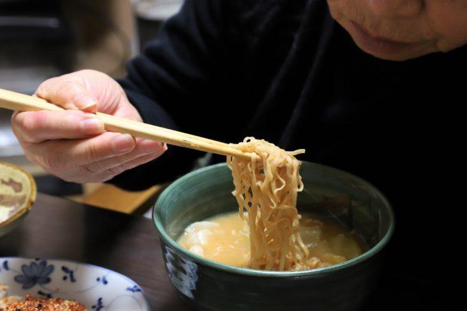 チキンラーメンの麺を、祖母(おばあ)が箸で摘まんでいるところ