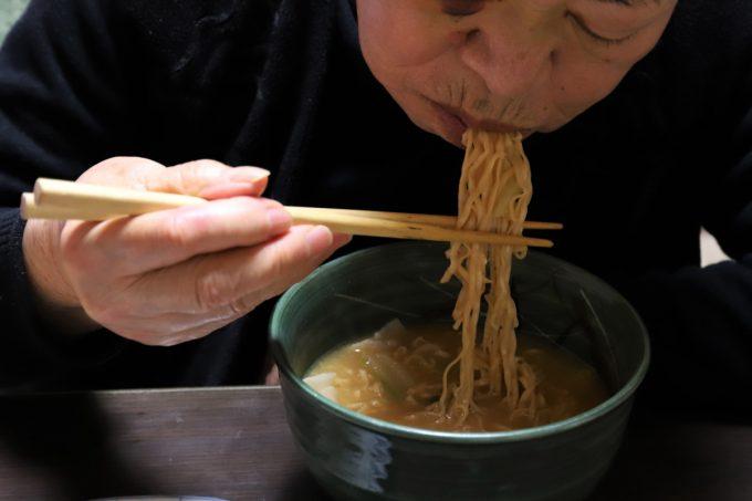チキンラーメンの麺を祖母(おばあ)が口煮れているところ