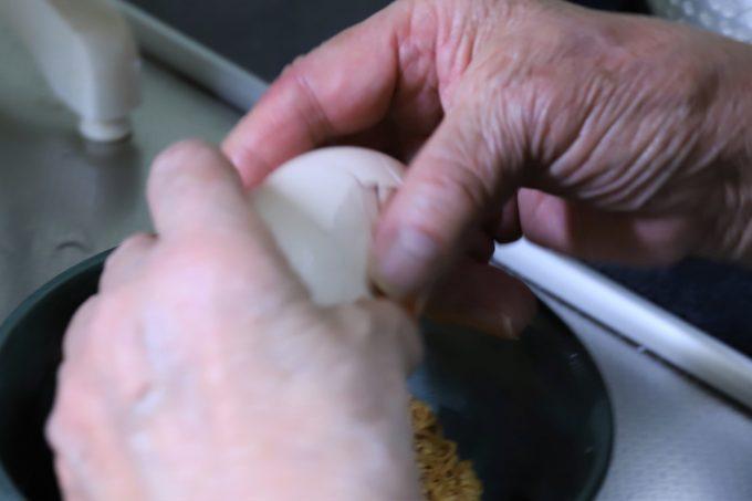 チキンラーメンの上で、祖母が生卵を割っているところ