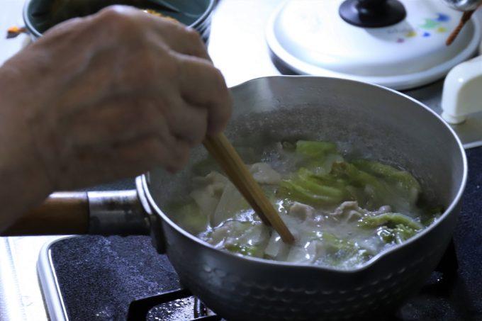 チキンラーメンにかけるために、野菜と豚肉を入れた湯を沸かしているところ
