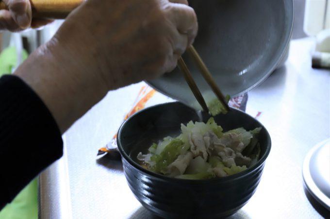 チキンラーメンの上に、白菜と豚肉を茹でたお湯をかけているところ