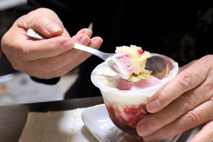 フルーツケーキのイチゴクリームとスポンジをスプーンですくっているところと