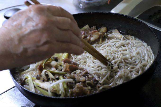 豚肉のすき焼きに蕎麦を入れて、祖母(おばあ)が菜箸で混ぜているところ