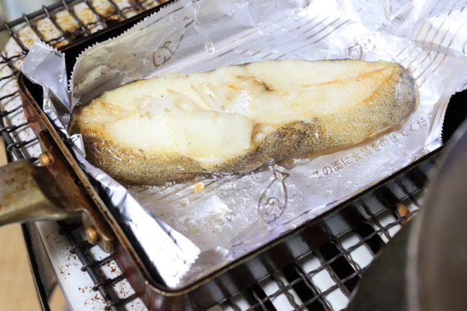 ストーブの上で焼いているムツらしき魚の切り身