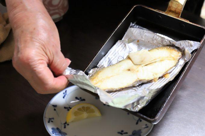 ムツらしき焼き魚を皿に移す祖母(おばあ)
