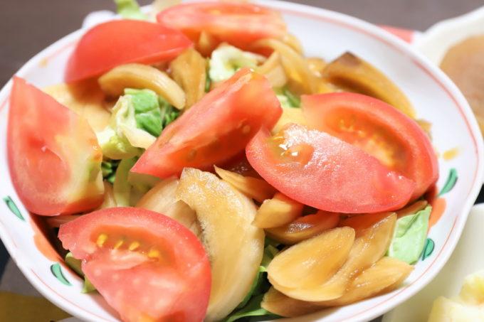 祖母(おばあ)が作ったトマトと玉ねぎの醤油漬けをのせた野菜サラダ