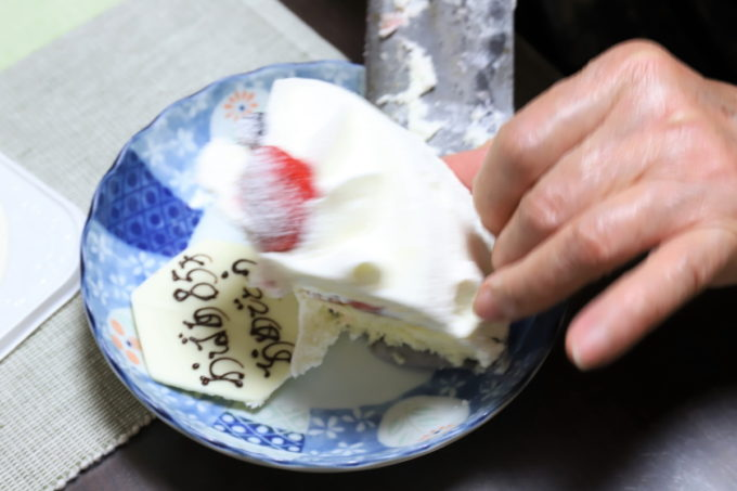 誕生日ケーキを取り分けている祖母