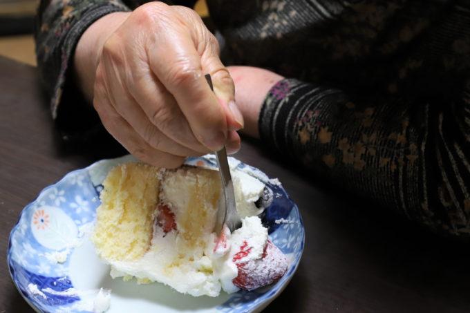 誕生日ケーキのイチゴにフォークを刺している祖母(おばあ)