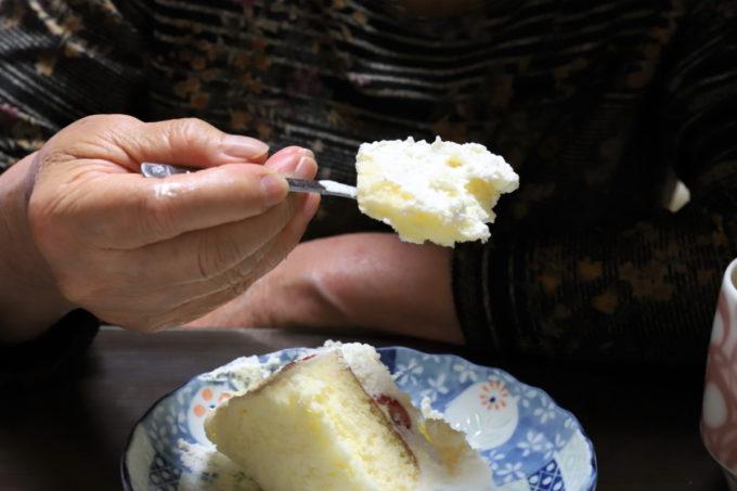 誕生日ケーキをフォークに載せている祖母