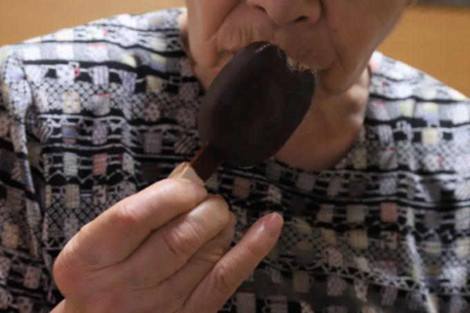 食べかけの森永チョコレートアイスクリームバーPARM(パルム)を手に持つ祖母(おばあ)