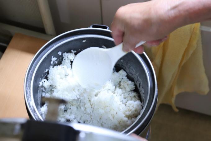 炊飯器からしゃもじでご飯をすくう祖母