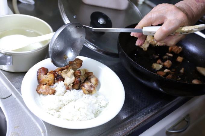 ご飯の上に炒めた鶏肉を載せているところ