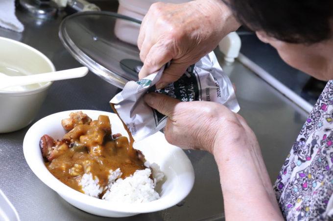 ご飯と鶏肉の上に、レトルトカレー(日本ハム「レストラン仕様カレー」(辛口)をかけているところ