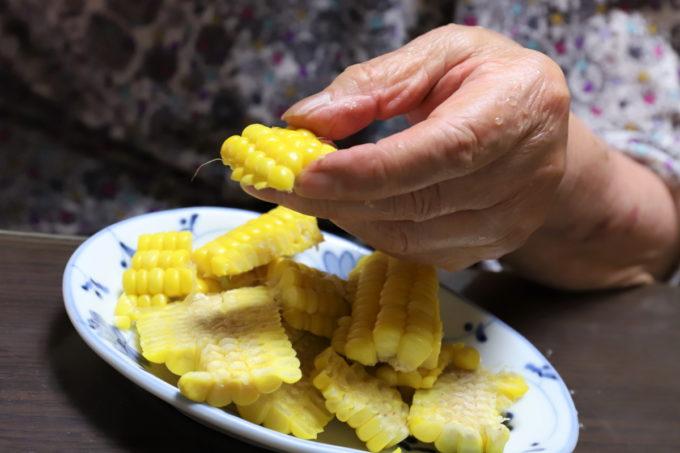 トウモロコシの実を摘まんでいる祖母(おばあ)
