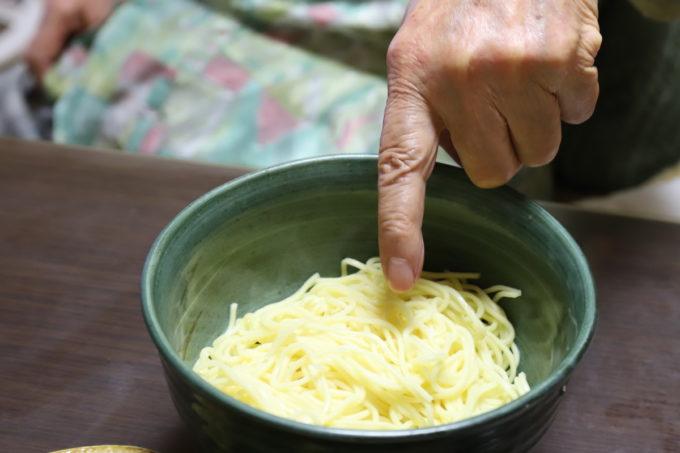 つけ麺の麺を指さす祖母の手