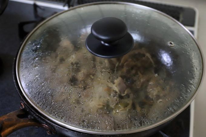 「炊いた肉」が入ったフライパンにフタがしてあるところ