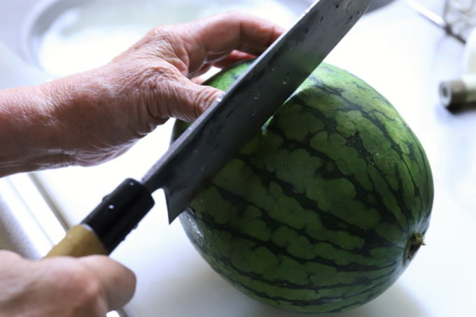 おばあが小玉スイカを包丁で切っているところ