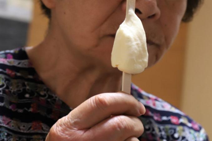 祖母(おばあ)が手に持つ明治「北海道バニラバー」