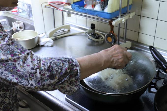 味の素冷凍ギョーザを焼いているフライパンのフタを取っているところ