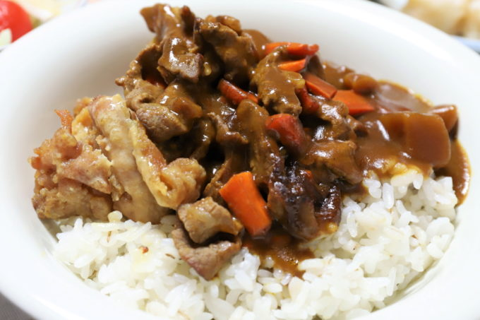 日本ハムのレトルト「レストラン仕様カレー」にマスタードチキンや牛肉などを加えたカレーを皿に盛ったところ