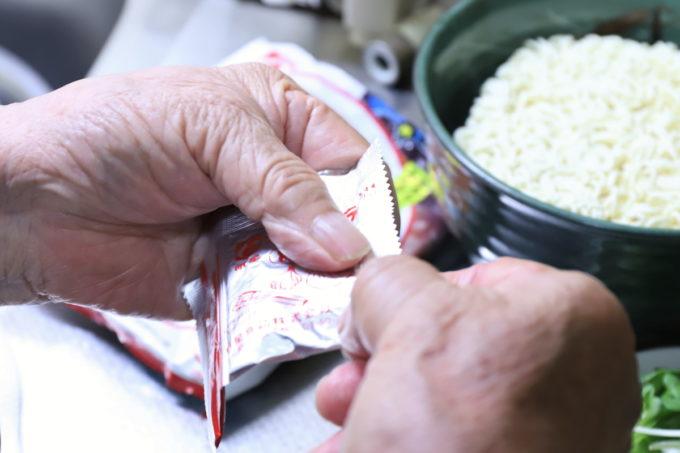 明星「チャルメラ」の粉末スープの袋を開けているところ