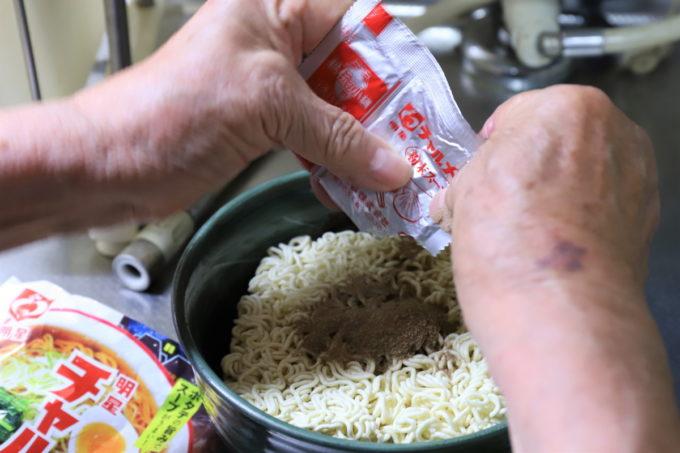 明星「チャルメラ」の麺に粉末スープをかけているところ