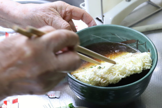 明星「チャルメラ」の麺を菜箸で押してスープに沈めているところ