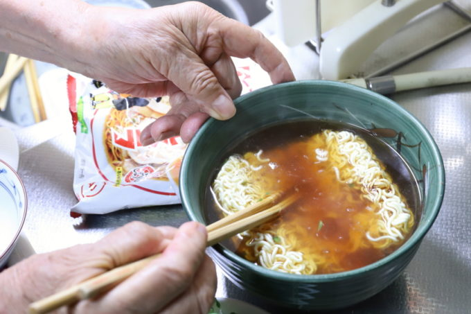 明星「チャルメラ」の麺を菜箸で押さえているところ
