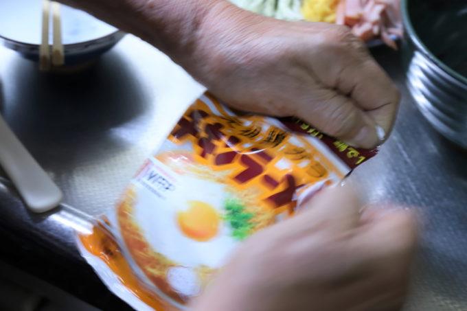 チキンラーメンの袋を開けている祖母(おばあ)の手