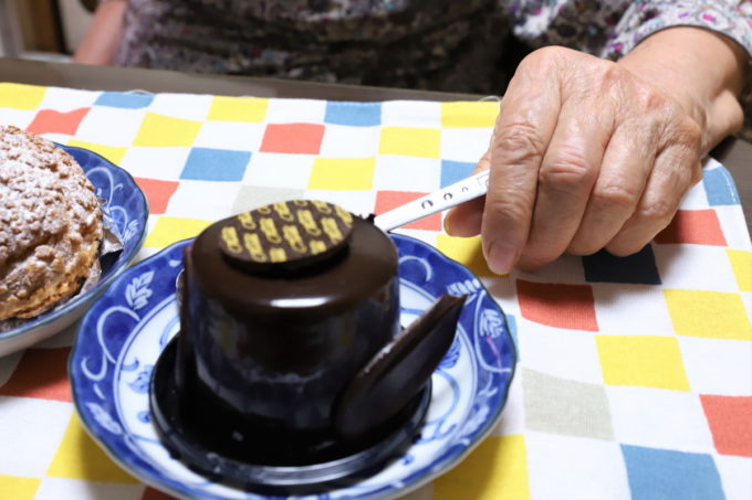 チョコレートケーキのスプーンを摘まむ祖母