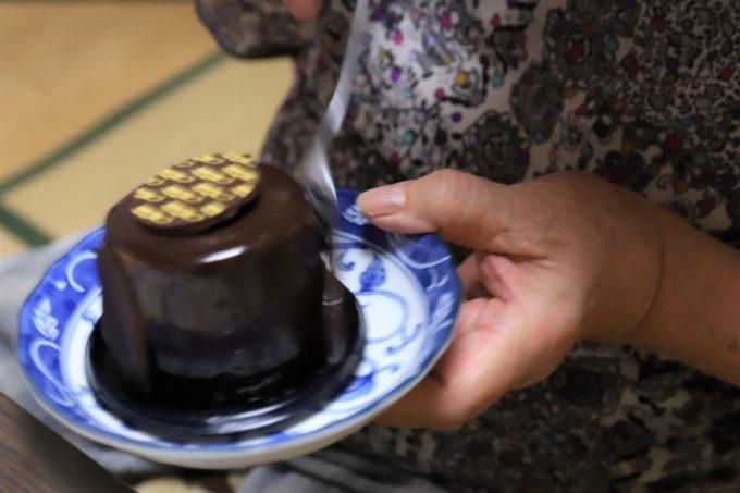敬老の日にプレゼントされたチョコレートケーキに祖母(おばあ)がスプーンを突き立てているところ