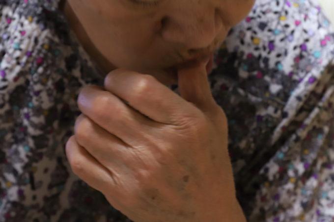 敬老の日のケーキを食べた後に指を舐めている祖母