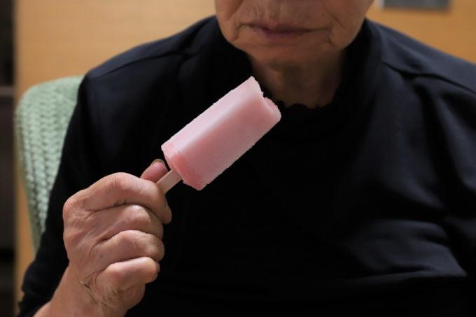 ピンクのアイスキャンディーを手に持つ祖母(おばあ)