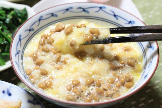たまごかけごはんに納豆を混ぜたものを、箸で摘まんで食べようとしているところ