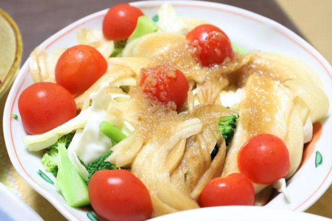 ミニトマトや玉ねぎの醤油漬けが乗った野菜サラダ(たいめいけんの玉ねぎドレッシングかけた)