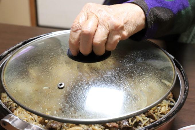 すき焼きの鍋のフタのつまみを手で持ち、開けるところ