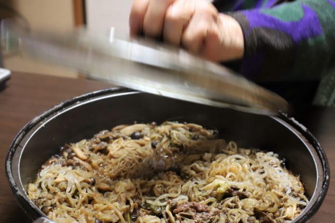 すき焼きの鍋のフタを手で持って開けている瞬間