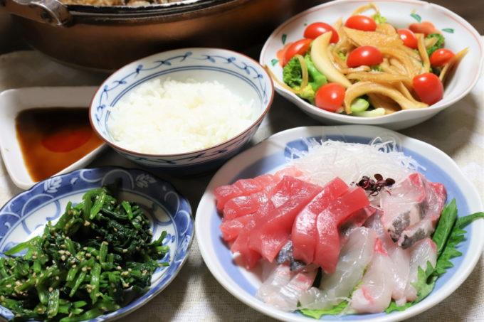 食卓に乗った晩ごはんの献立(刺身やほうれん草のおひたし、サラダ、すき焼き)
