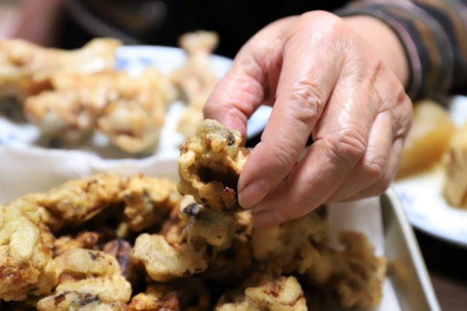 祖母(おばあ)が手で牡蠣の天ぷらを摘まんでいるところ