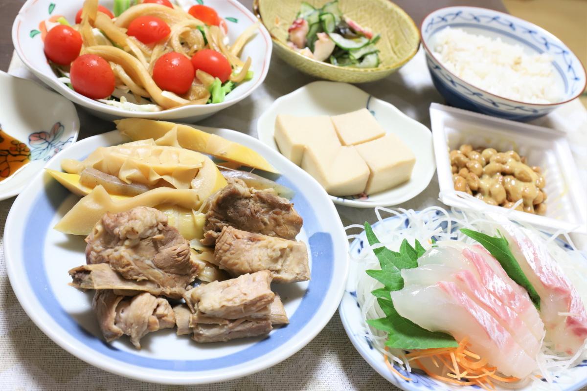 祖母(おばあ)が作った骨付き豚肉とタケノコの煮物や鯛の刺身、納豆など、タンパク質たっぷりの晩ごはん