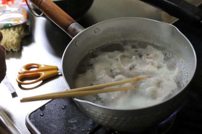 サッポロ一番味噌ラーメンをつくるために、鍋で豚肉を茹でているところ