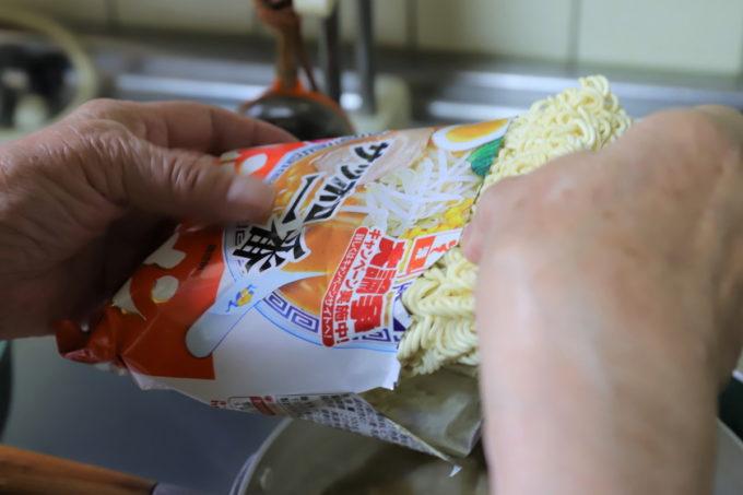 サッポロ一番味噌ラーメンの麺を手でつかんでいるところ