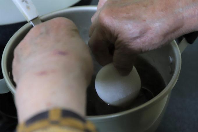 雑煮の鍋に餅を入れる祖母(おばあ)