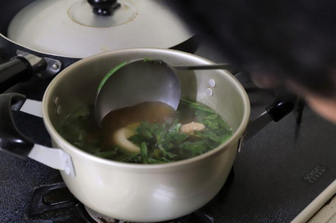 鍋の中の雑煮をお玉ですくっているところ