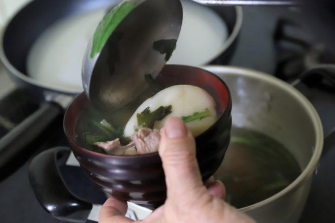 モチ入りの雑煮をお椀に入れているところ