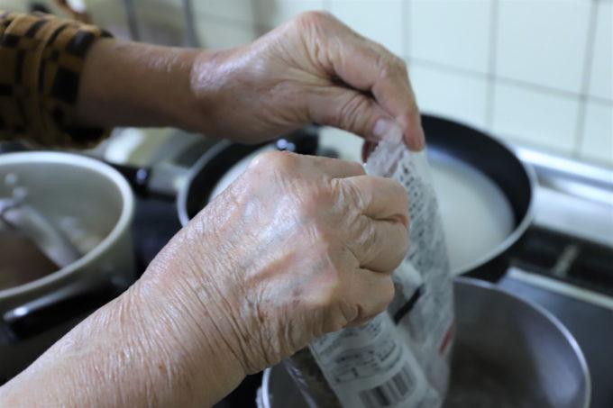 年越しそばの袋を開ける祖母(おばあ)の手