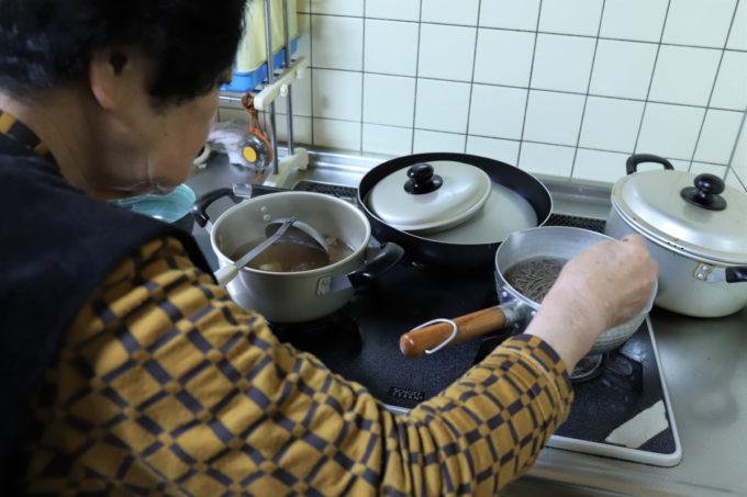 茹でている蕎麦を菜箸で混ぜている祖母(おばあ)
